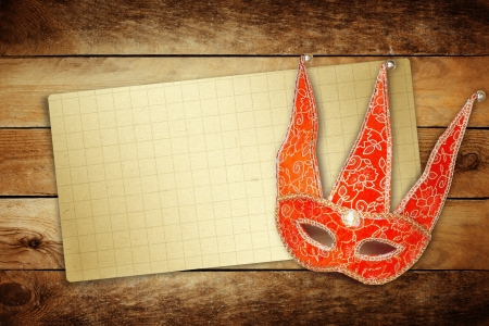 Carnival red mask with old paper for greeting on wooden background  photo