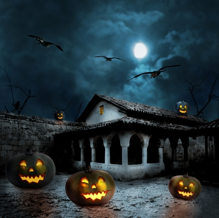 Halloween pumpkins in the yard of an old house at night in the bright moonlight photo