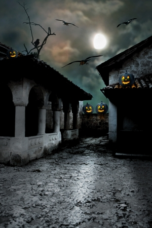 Halloween pumpkins in the yard of an old house at night in the bright moonlight