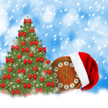 Santa Claus hat, clock and Christmas tree. Christmas snowy night photo