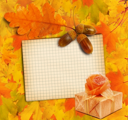 Old grunge paper with autumn oak leaves and Gift box on the wooden background photo