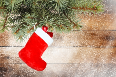 Red christmas boot with gifts on wooden wall Foto de archivo