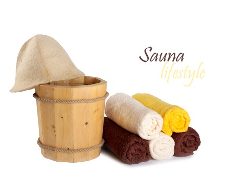 Wooden bucket with ladle for the sauna and stack of clean towels photo