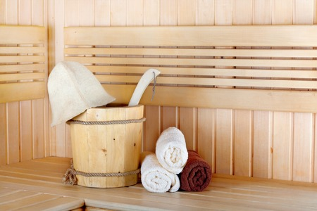 Traditional wooden sauna for relaxation with bucket of water and set of clean towels photo