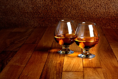 Two goblets of brandy on wooden old counter top  photo