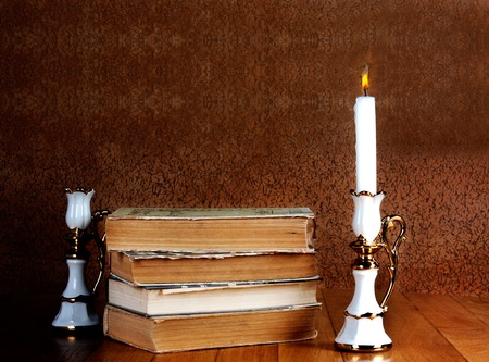 Old stack of books with candlestick and burning candle on the wooden table photo