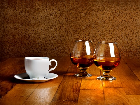 Two goblets of brandy and cup of hot coffeeon wooden old counter top  photo