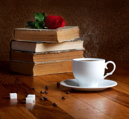 Hot cup of fresh coffee on the wooden table and stack of books to read with red rose photo