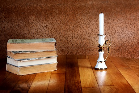 Old stack of books with candlestick and burning candle on the wooden table Stock Photo - 26509538