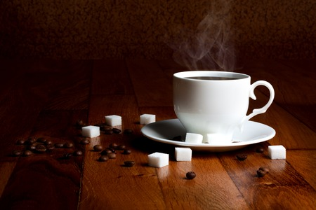 Fresh cup of hot coffee with sugar and natural grains on a wooden table photo