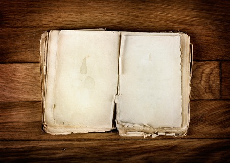 Open old book with blank pages for text on vintage wooden table photo