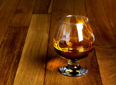 One glass of brandy on antique wooden counter top  photo