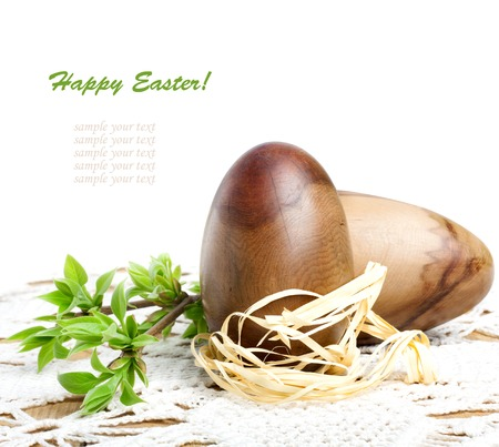 Decorative wooden Easter eggs with green branch on a beautiful lace tablecloth photo