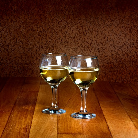 Two wineglasses of white wine on wooden old counter top photo