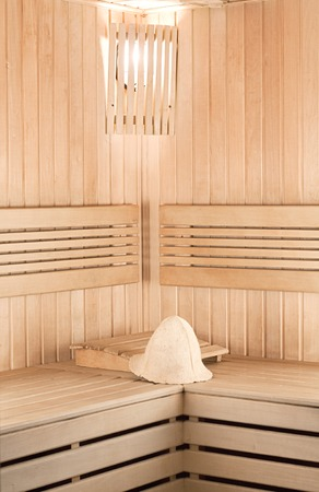 Traditional wooden sauna for relaxation with felt hat photo