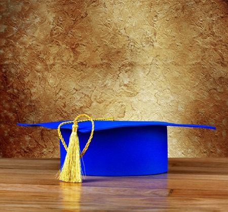 Graduation mortarboard on wooden table on background of vintage wall photo
