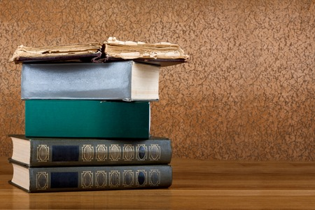 Pile of old books on a beautiful wooden table photo