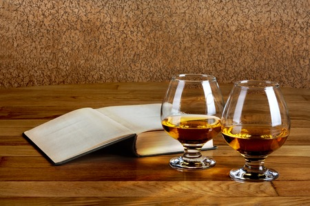 Two goblets of brandy and open book on wooden old counter top photo