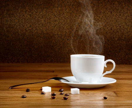 Hot fresh coffee in a white cup with sugar on wooden table photo