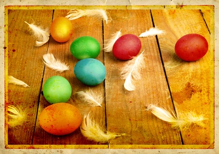 Grunge old carved postcard with eggs to celebrate Easter on the wooden background  photo