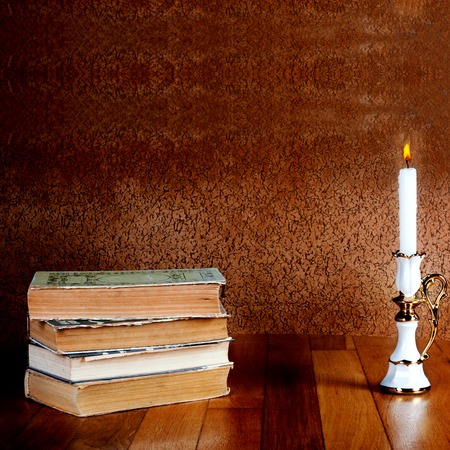 Old stack of books with candlestick and burning candle on the wooden table Stock Photo - 27403711