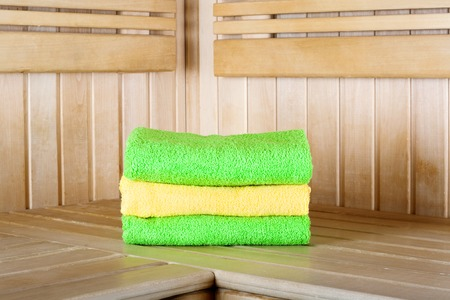 Traditional wooden sauna for relaxation with set of clean towels photo