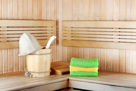 body temperature: Traditional wooden sauna for relaxation with bucket of water and set of clean towels