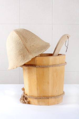 Wooden bucket with ladle for the sauna on white background photo