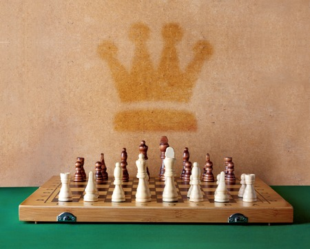 Wooden chess board with figures on green table and old wall photo