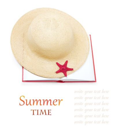 Straw hat with book and red starfish isolated on white background photo