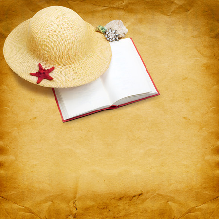 Straw hat with book and red starfish on shabby paper background photo