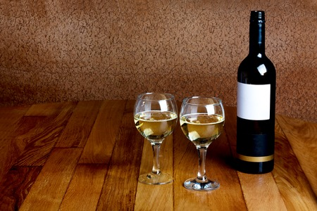 Bottle of white wine and two glasses on  wooden table top photo