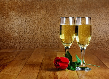 Two glasses of champagne with artificial red rose on wooden tabletop photo