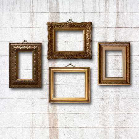 Gilded wooden frames for pictures on old stone wall photo