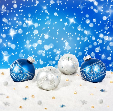 Blue and silver Christmas balls on snow background with stars photo