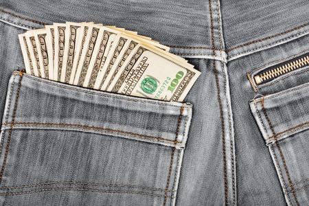 A hundred dollar bills sticking in the back pocket of denim black jeans photo