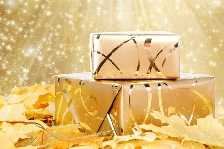 Gift box in gold wrapping paper with autumn leaves on the abstract glowing background photo
