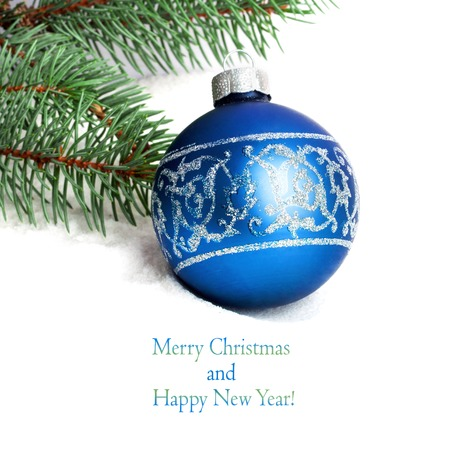 Blue Christmas ball and green spruce branch isolated on white background photo