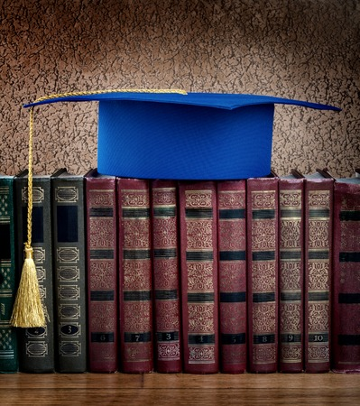 Graduation mortarboard on top of stack of books on abstract background of wall photo