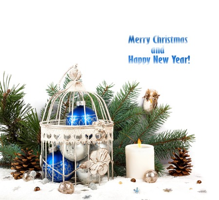 Blue and silver christmas balls in a cage on the background of fir branches and candles photo