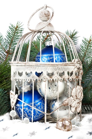 Blue and silver christmas balls in cage on the background of fir branches