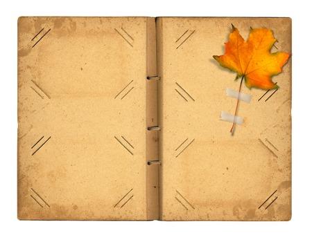 Open vintage photoalbum for photos with autumn foliage on white isolated background