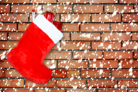 Red christmas boot with gifts on background brick wall photo