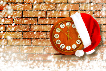 Santa Claus hat on New Years night on the old clock showing twelve oclock on the brick background photo