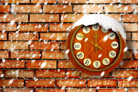 Snow-covered clock on background of old brick wall photo