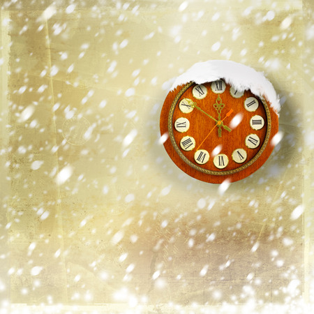 Snow-covered clock on abstract gold background photo