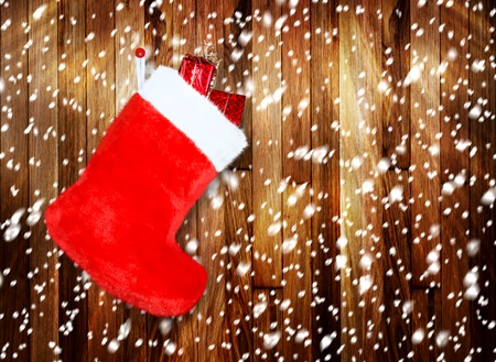 Red christmas boot with gifts on background wooden wall photo