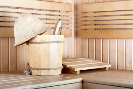 Traditional wooden sauna for relaxation with bucket of water photo