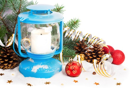 Snowy blue lantern and Christmas balls on the background of fir branches photo