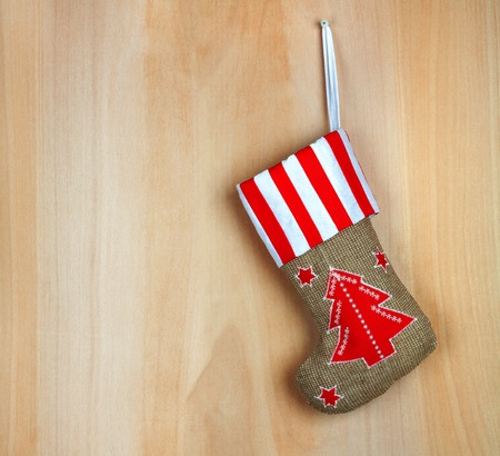 hessian boots: Red christmas boot with gifts on background wooden wall